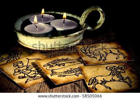 astrology and its zodiac symbols with three candles - stock photo