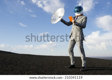 Astronaut businessman traveling into the future of communication with satellite receiver for his tablet on dramatic lunar landscape - stock photo