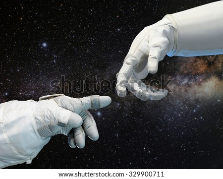 Astronaut hand and robotic hand on outer space background. Elements of this image furnished by NASA. - stock photo