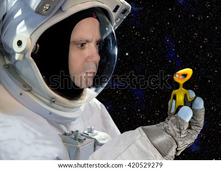Astronaut holding in glove alien on background of stars. Cosmonaut in space has meeting with aliens.