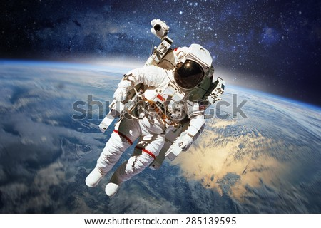 Astronaut in outer space with planet earth as backdrop. Elements of this image furnished by NASA. - stock photo