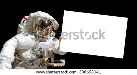 Astronaut in space holding a white blank board - elements of this image are provided by NASA - stock photo