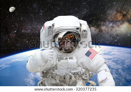 Astronaut on space mission with earth on the background. Elements of this image furnished by NASA. - stock photo