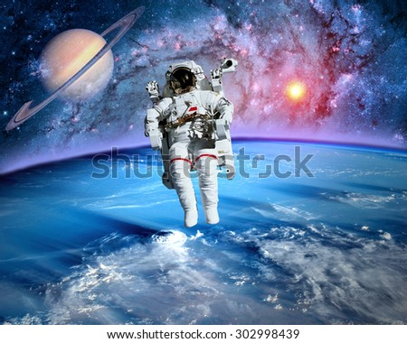 Astronaut spaceman outer space planet saturn earth sun universe. Elements of this image furnished by NASA. - stock photo