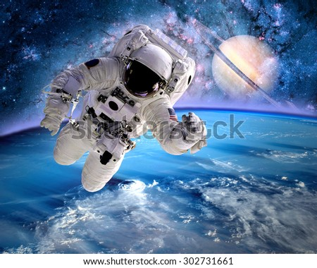 Astronaut spaceman outer space planet saturn earth universe. Elements of this image furnished by NASA. - stock photo