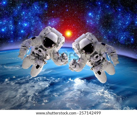 Astronaut spaceman outer space teamwork hands earth people. Elements of this image furnished by NASA. - stock photo