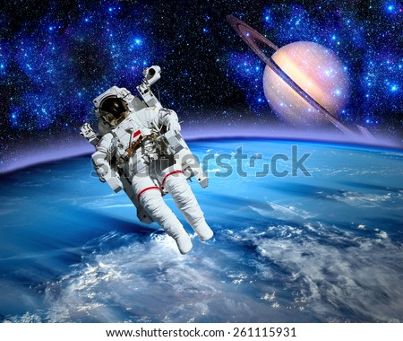 Astronaut spaceman space suit saturn planet earth. Elements of this image furnished by NASA. - stock photo