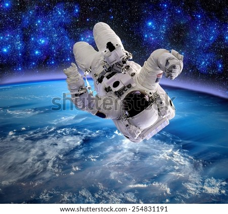 Astronaut upside down spaceman relax space suit stars. Elements of this image furnished by NASA. - stock photo