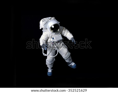 Astronaut wearing a pressure suit against a black background.   - stock photo