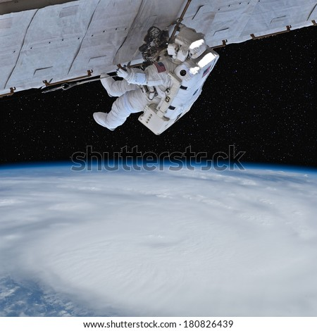 Astronaut works in orbit above the Earth. Stars in the background.  Elements of this image furnished by NASA.  - stock photo