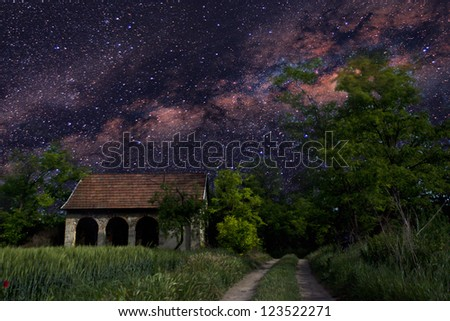 Astronomy photograph with small house in the forest. - stock photo