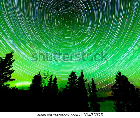Astrophotography star trails around the Polar Star or Polaris and green glowing display of Northern Lights or Aurora borealis in over taiga forest trees of Yukon Territory  Canada - stock photo