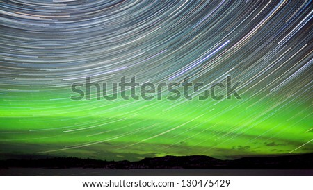 Astrophotography star trails with green glowing display of Northern Lights or Aurora borealis in Yukon Territory  Canada - stock photo