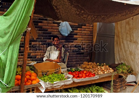 ASWAN - APRIL 28 2007:Egyptian man selling vegetables in Aswan farmers market, in Aswan Egypt. Egypt's total agricultural crop production has increased by more than 20 percent in the past decade. - stock photo