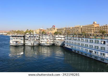 ASWAN, EGYYPT - FEBRUARY 2, 2016: Cruiseship Boats docked  along the shore of the Nile River at Aswan, Egypt - stock photo