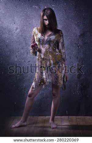 Asylum. Lonely mad woman with red apple in a dark room. Low key. - stock photo