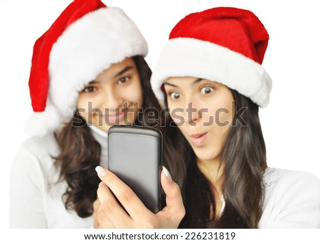 At Christmas Time.  Two beautiful girls taking self-portrait with mobile phone in Santa hats, isolated on white background. Focus on the Mobile Phone. - stock photo