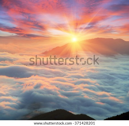 At dawn, after a warm rain ridges Chornogory haze enveloped with rays of sunshine. Sea fog in the pink light is very beautiful and fabulous, picturesque vague wave rolled on the slopes of the peaks - stock photo