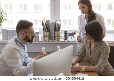 At doctor office. Doctor talking to patient after tests. Nurse standing near patient