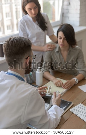 At doctor office. Doctor talking to patient after tests. Nurse standing near patient - stock photo