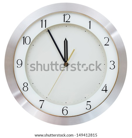 at five minutes to twelve on the dial round wall clock - stock photo
