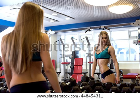 At gym. Sexy woman selects dumbbells for training - stock photo