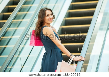 At her way to the next store. Rear view of beautiful young woman with shopping bags on mall escalator - stock photo