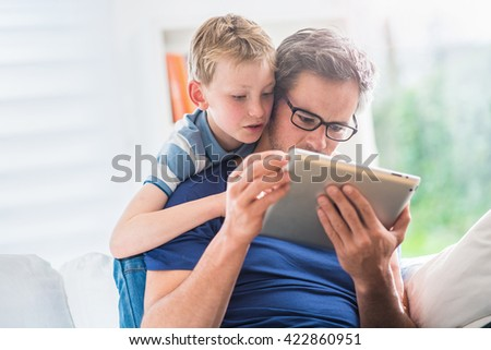 At home, a father and his young son having fun by gaming on a tablet, dad sits on a white couch and the boy looks at the screen over the shoulder of his father and giving him advices to win.  - stock photo