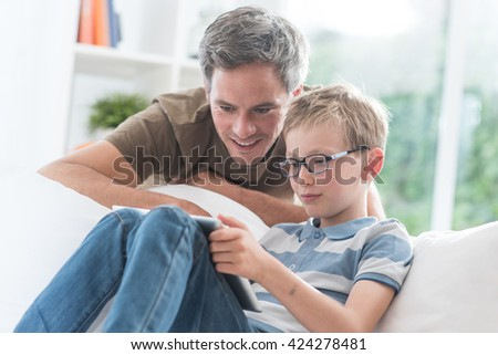 At home, a father and his young son having fun by gaming on a tablet, kid sits on a white couch and dad looks at the screen over the shoulder of his son and giving him advices to win - stock photo