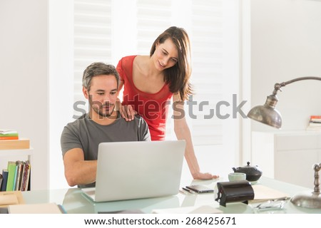 at home, a modern couple preparing their next vacation destination on a laptop, their home is modern and bright - stock photo