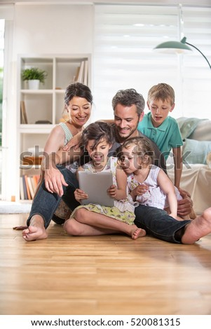 At home, Cheerful family of five person is sitting on wooden floor in the living-room. They are watching a movie on a digital tablet
