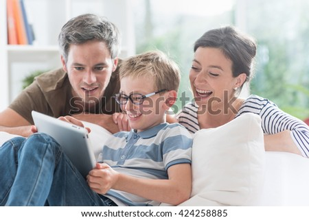 At home, Dad, mom and their young son having fun by playing together on a tablet, they are sitting on a couch in the living room and the parents look at the screen over the shoulder of their kid  - stock photo