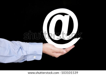 At letter - internet symbol -  held in hand over black background - stock photo