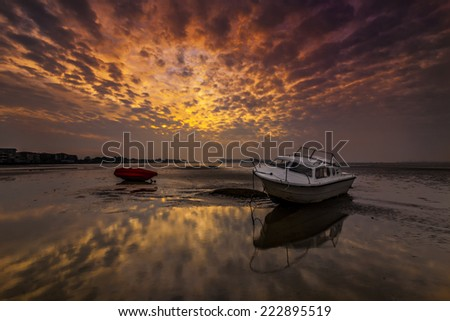 At low tide boats lie high and dry on the shore of Poole Harbor at Sandbanks under a setting sun - stock photo