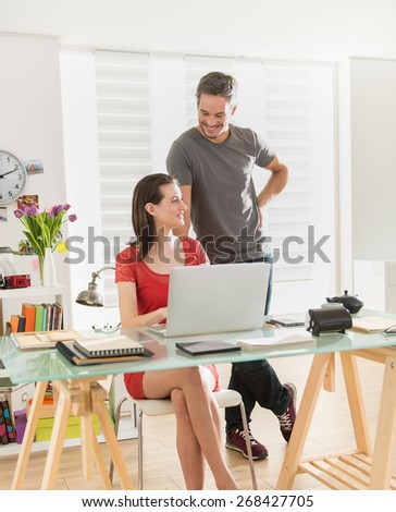 At office two colleagues examining a project together on a laptop, the office is modern and bright - stock photo