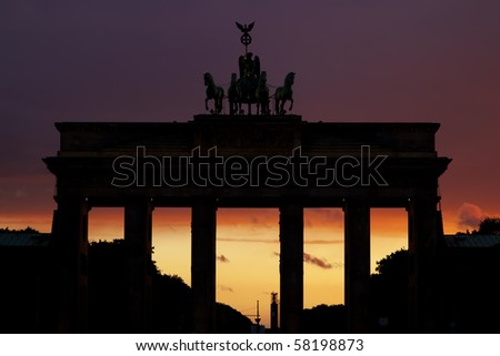 At sundown, the silhouette of the famous brandenburger tor in front of red and purple sky in Berlin, germany - stock photo