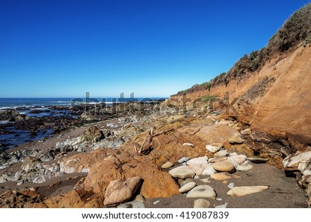 At sunrise, blue sky, tidal pools, unusual geological formations, with rock-boring mollusk holes, at low tide, along the rugged Big Sur coastline, near Monterey, CA. on the California Central Coast. - stock photo