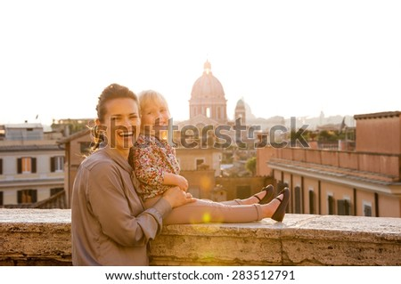 At sunset, a brunette mother standing behind her blonde daughter, holding her, as she is sitting on a ledge above the city of Rome. Both are happy and smiling. In the distance, St. Peter's Basilica. - stock photo