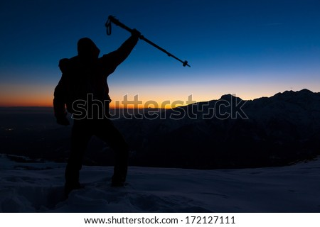At sunset a man stands on a snowy peak expressing his joy for have reached the top of a mountain peak. Concept: adventure, achievement, sport. - stock photo