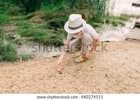 at sunset, playing with a green frog on the river a little boy in a hat - stock photo
