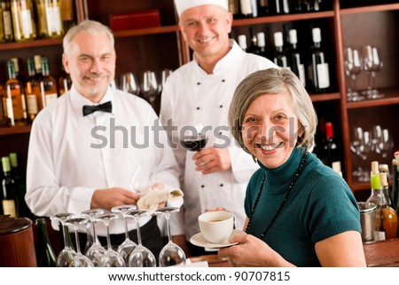 At the bar - happy senior people having drink - stock photo
