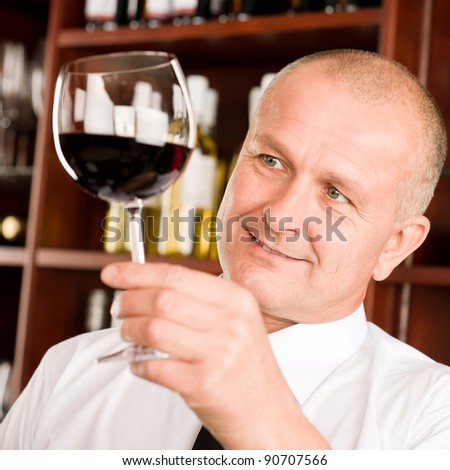At the bar - senior barman hold glass red wine degustation - stock photo