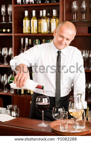 At the bar - waiter pour red wine in glass restaurant - stock photo
