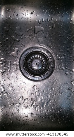 At the base of the kitchen wash basin is a strainer. Both sink and strainer are made of stainless steel. Strainer acts as a waste food stopper and filter. Stainless steel is hygienic and non-porous. - stock photo