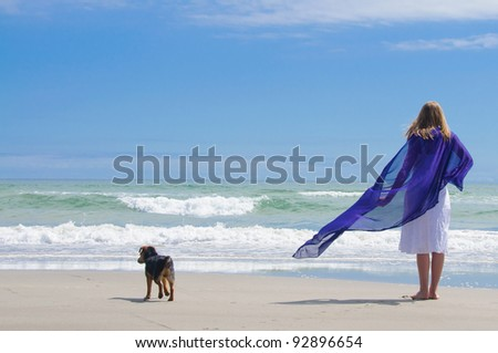 At the beach with dog watching the waves - stock photo