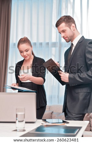 At the business meeting. Two cheerful business people in formal wear looking at the laptop together and pointing at something - stock photo