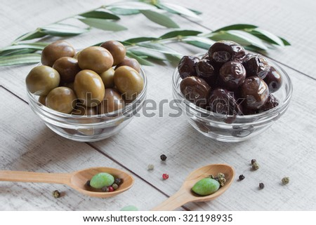 At the center of horizontal frame 2 glass bowls with different olives framed by branches of the olive tree, wooden spoons with olives on wooden white background. Green and black kinds of olives.  - stock photo
