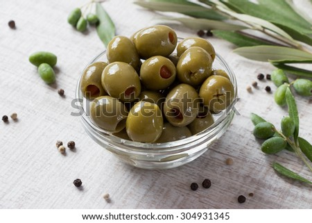 At the center of the frame bowl with green olives stuffed with pepper framed by olive tree branches and scattered peppercorns . Green olives stuffed with red pepper. Horizontal shot.. Daylight. - stock photo
