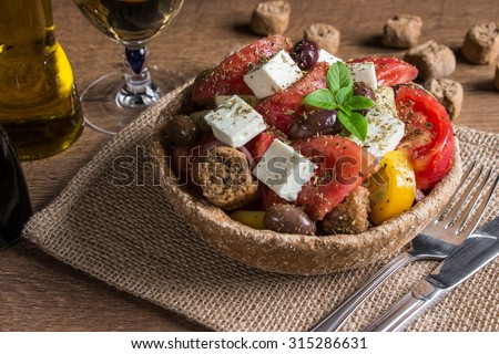 At the center of the frame bread bowl of Greek salad on a table-napkin of burlap in the background olive oil, balsamic vinegar, glass of wine, croutons.  Cretan Greek salad for lunch. Horizontal.    - stock photo