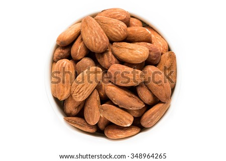 At the center of the frame white bowl with roasted almond kernels no added salt on a white background. Roasted almond kernels. Close. Horizontal shot. Top view. - stock photo